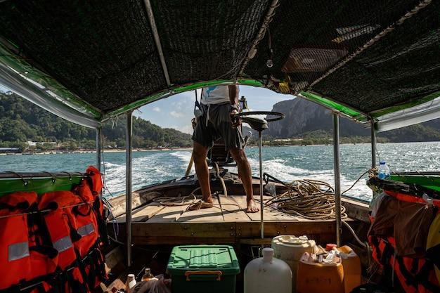 Starker mann, der ein boot fährt und eine neue insel besuchen will