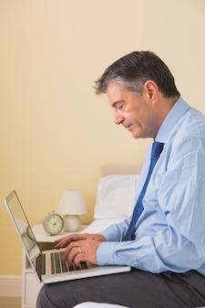Starker mann, der einen laptop sitzt auf bett verwendet