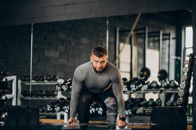 Starker mann, der im fitnessstudio trainiert