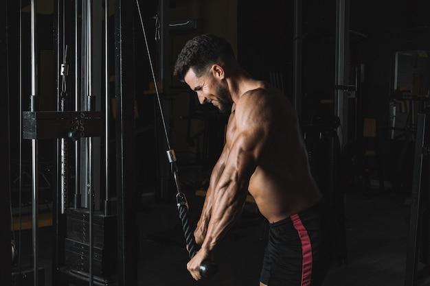 Starker mann, der in einem fitnessstudio von einer waage zieht