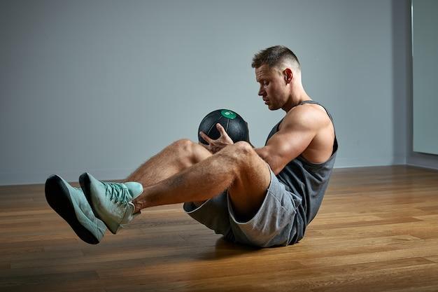 Starker mann, der übung mit med ball macht. foto des perfekten körpers des mannes auf grauer wand. kraft und motivation.