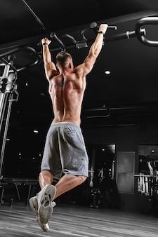 Starker mann, der übungen im fitnessstudio macht