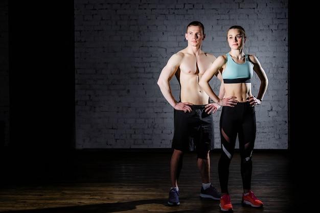 Starker mann des bodybuildings und eine frau, die auf einem backsteinmauerhintergrund aufwirft