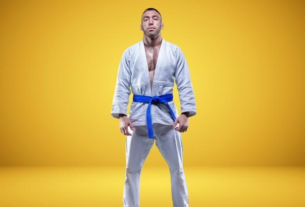 Starker mann im kimono mit blauem gürtel. gelber hintergrund. kampfkunst-konzept. gemischte medien