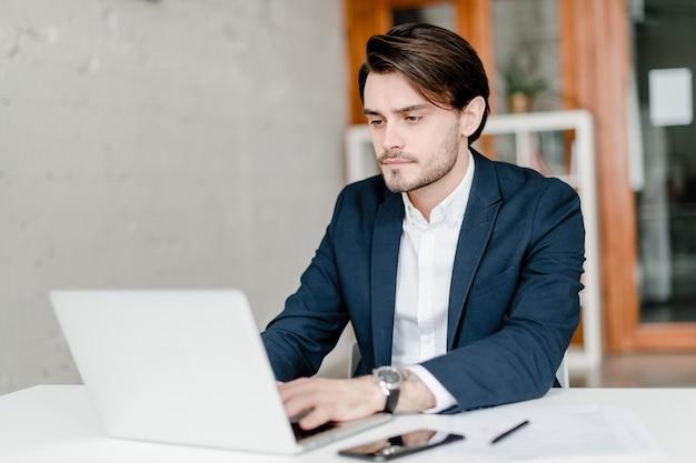 Starker mann in der klage schreibend auf laptop im büro