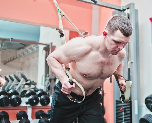 Starker mann macht crossfit liegestütze mit fitnessgurten im fitnessstudio