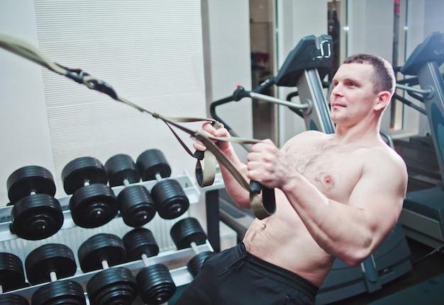 Starker mann macht crossfit-training mit fitnessgurten im fitnessstudio