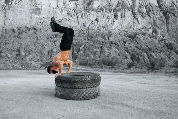 Starker mann mit nacktem oberkörper, der liegestütze auf zwei reifen im sandsteinbruch macht. aktiver mann mit schwarzer gesichtsmaske und sporthose. konzept des trainings im freien.
