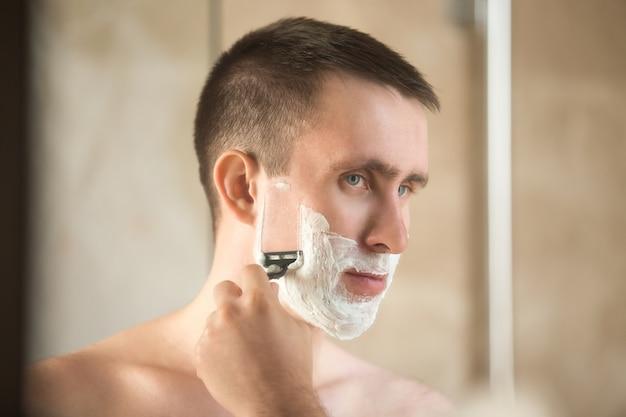Starker mann, seine wange rasieren