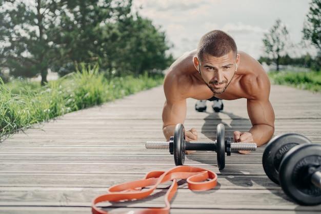 Starker motivierter gutaussehender mann steht in plankenhaltung