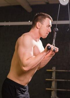Starker muskulöser bodybuilder, der übung im fitnessstudio macht