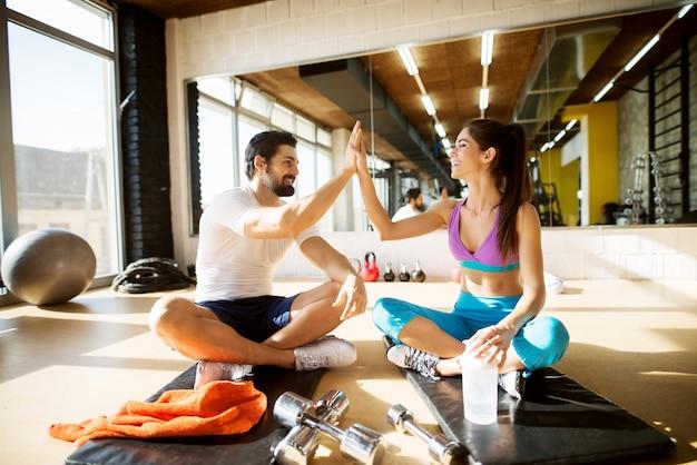Starker muskulöser fröhlicher glücklicher bärtiger mann, der auf der schwarzen matte sitzt und hände mit seiner entzückenden lächelnden form-fitness-freundin klatscht, während er für eine pause im fitnessstudio neben ihm sitzt.