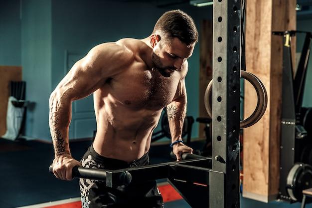 Starker muskulöser mann, der liegestütze auf stufenbarren in crossfit turnhalle tut