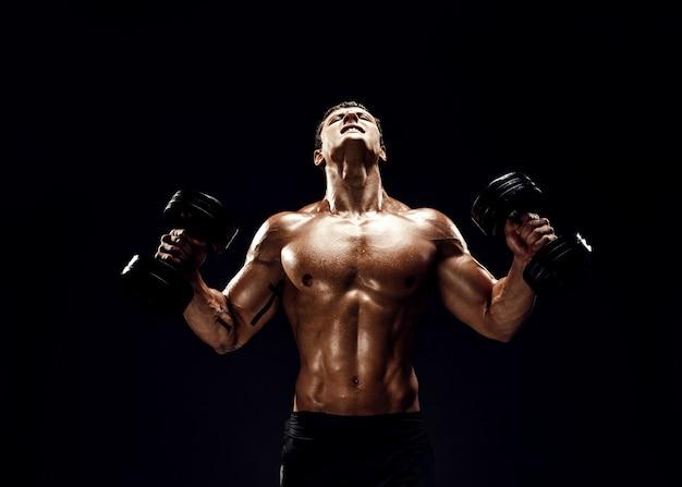 Starker muskulöser mann, der übung mit dummköpfen tut
