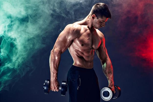 Starker muskulöser mann, der übung mit dummkopf tut