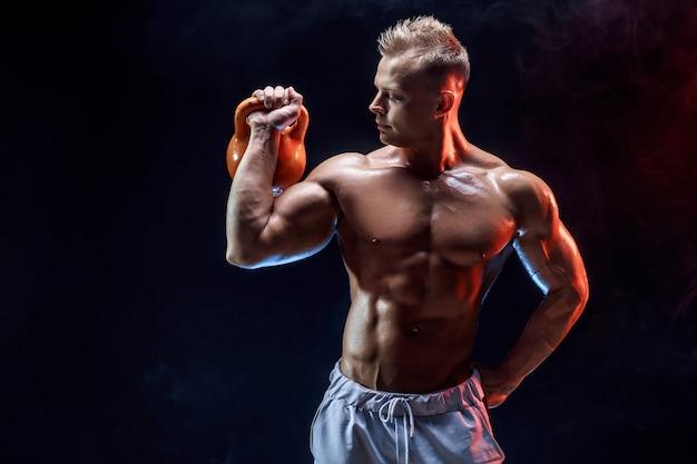 Starker muskulöser mann, der übung mit kettlebell tut