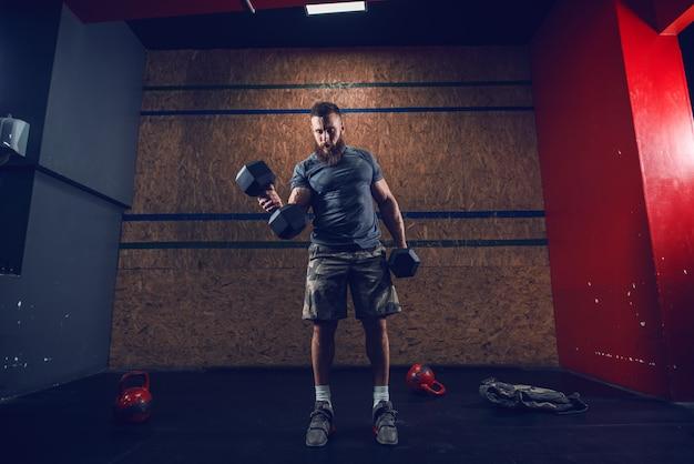 Starker muskulöser mann im t-shirt und in den kurzen hosen, die hanteln heben, während sie im fitnessstudio stehen. gesundes lebensstilkonzept.