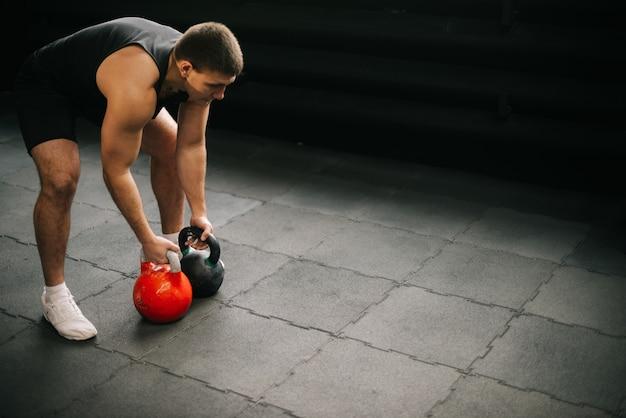 Starker muskulöser mann mit perfektem, schönem körper, der sportkleidung trägt, die schwere freie gewichte hebt