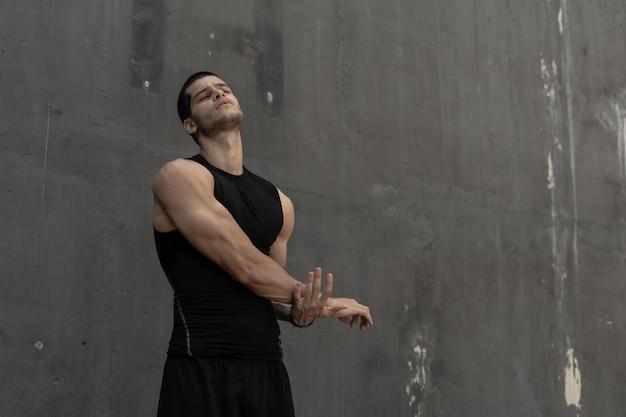 Starker muskulöser, sportlicher mann, der sich aufwärmt und sich auf traini vorbereitet