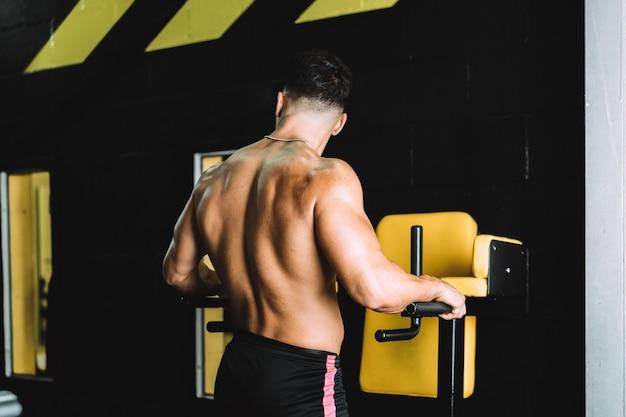 Starker nackter rücken eines erwachsenen kaukasischen mannes, der in einem fitnessstudio trainiert