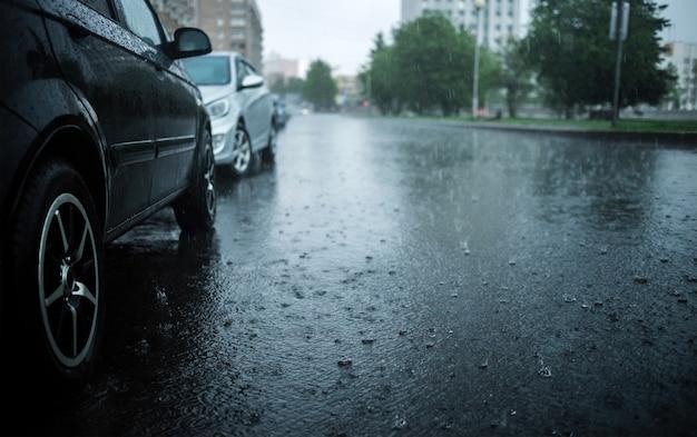 Starker regen in der stadt. stadtstraße mit regen, wasserleitung überflutet
