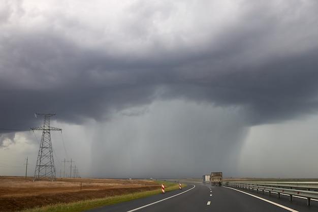 Starker regen strömt aus einer wolke, die über der autobahn hängt