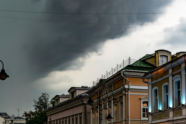 Starker regen und massive wolken, die über die europa-stadtdächer fliegen