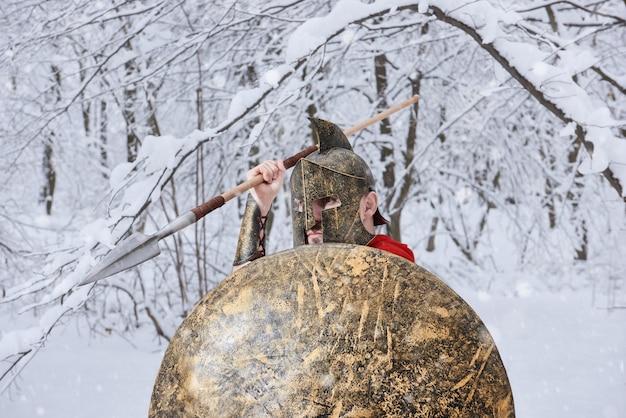 Starker spartanischer krieger wartet im verschneiten wald auf gefahr