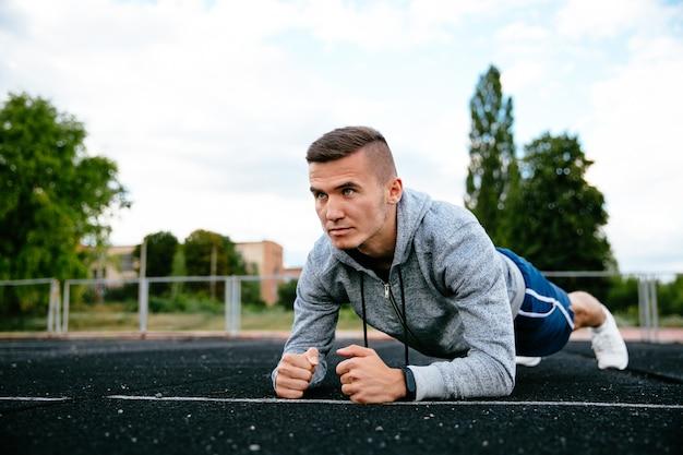 Starker sportler, der plankenhaltung tut, übung, ausarbeitend, gekleidet in der grauen sportjacke