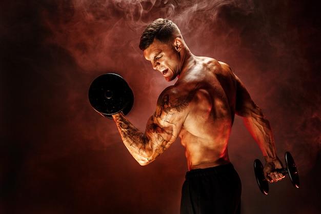 Starker sportler, der schweren dummkopf im rauche anhebt
