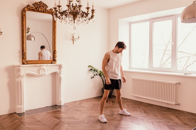 Starker, sportlich fitter mann in t-shirt und shorts macht zu hause in seinem geräumigen und geräumigen ...