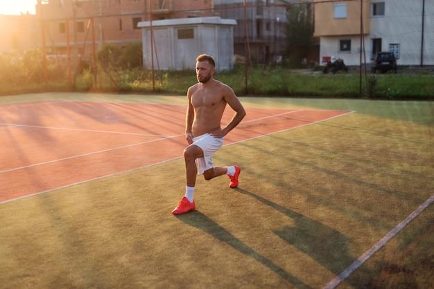 Starker sportlicher mann, der seine beine vor dem training streckt. stehen im tennisspielplatz am heißen sommermorgen.
