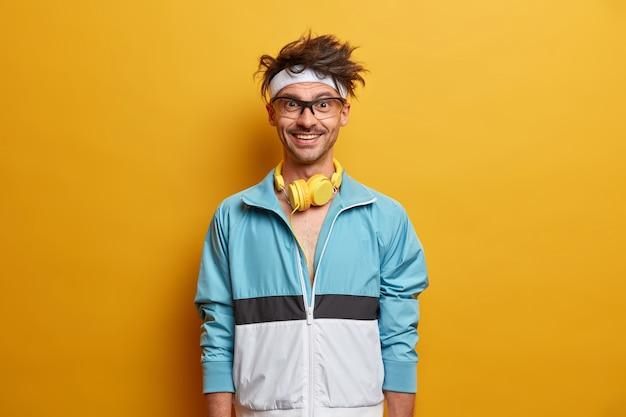 Starker sportlicher mann mit fröhlichem ausdruck, glücklich zu trainieren, hört musik in kopfhörern, trägt sportbekleidung, ist gut gelaunt, will stark und gesund sein. sport- und feuchtigkeitskonzept