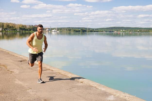 Starker sportmann, der beim training in der nähe der stadt am fluss joggt. Premium Fotos