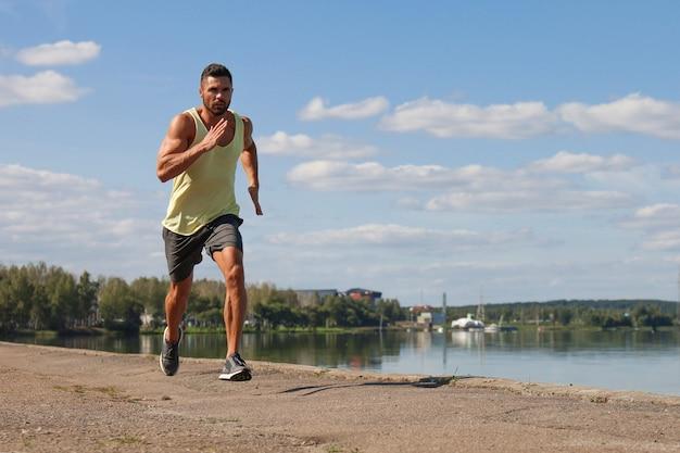 Starker sportmann, der beim training in der nähe der stadt am fluss joggt.