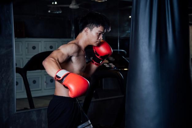 Starker sportmannboxer des jungen mannes machen übungen in der turnhalle, gesundes konzept