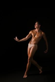 Starker tänzer, der vorwärts tritt und hand bewegt
