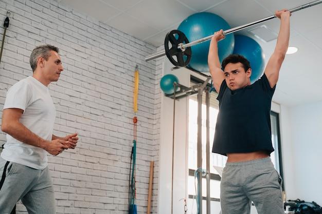 Starker und muskulöser junger mann in seinen 20ern, der mit der motivation eines personal trainers krafttraining für das gewichtheben macht