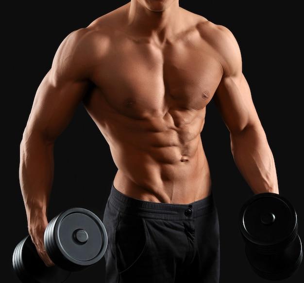 Starker und muskulöser männlicher bodybuilder, der hanteln auf schwarz hält