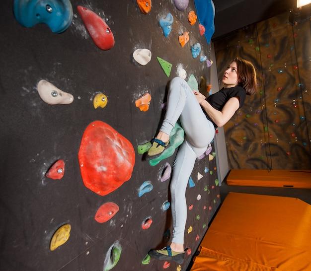 Starker weiblicher bergsteiger auf der flusskletterwand innen