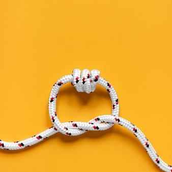 Starker weißer seilknoten auf orangeem kopierraumhintergrund