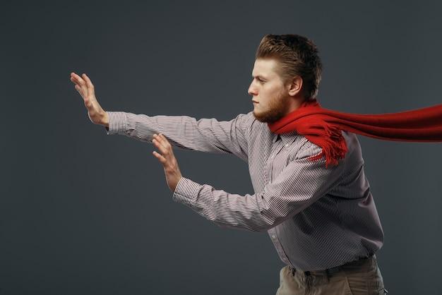 Starker wind weht auf mann im roten schal, lustige emotion. leistungsstarker luftstrom bläst auf geschäftsmanngesicht