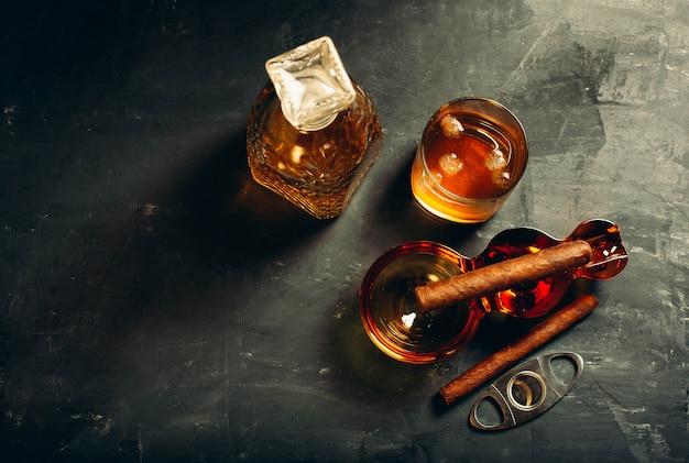 Starkes alkoholisches getränk, scotch whisky ich mit rauchender zigarre im aschenbecher auf grau