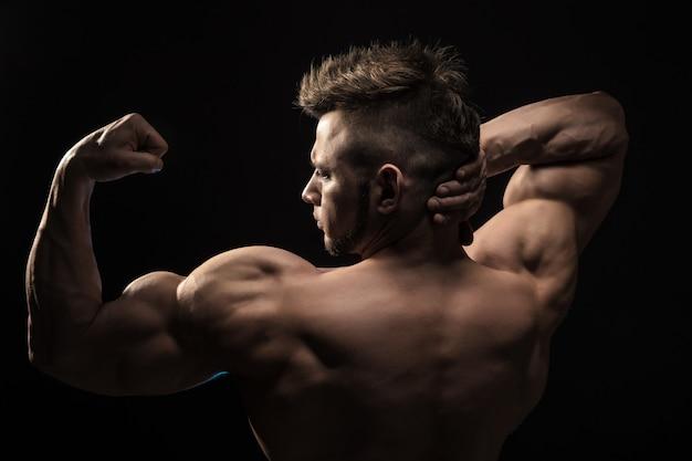 Starkes athletisches mann-eignungs-modell, das rückenmuskulatur aufwirft.