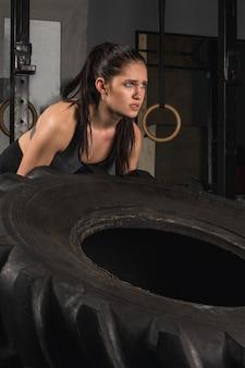 Starkes mädchen, das einen reifen im fitnessstudio umdreht.