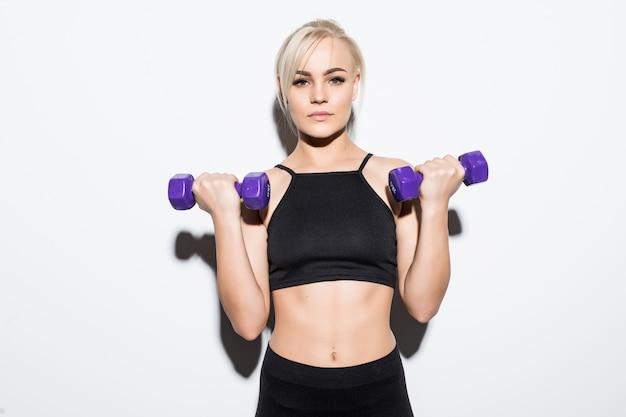 Starkes muskulöses blondes mädchen, das sich auf einen wettbewerb mit blauen hanteln auf weiß vorbereitet