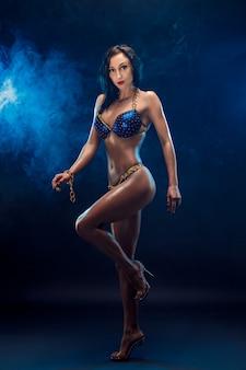 Starkes, muskulöses sport-mädchen im bikini, der die kamera steht und betrachtet