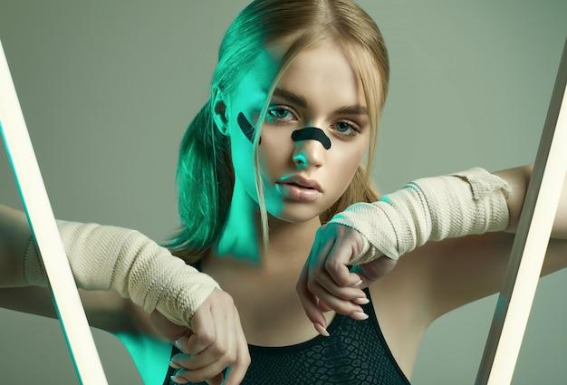 Starkes schönes mädchen mit blonden haaren, selbstbewusstem blick, fäuste in schützenden boxverbänden