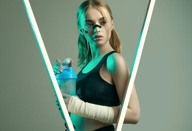 Starkes schönes mädchen mit blonden haaren, sportfigur, selbstbewusstem blick, fäuste in schützenden boxverbänden