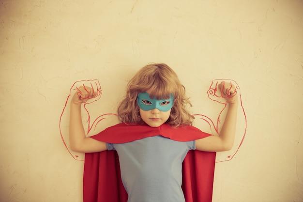 Starkes superheldenkind mit gezogenen muskeln. frauenpower und feminismus-konzept